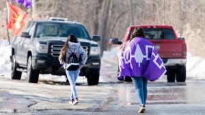 People walk towards a blockade on the Kahnawake Mohawk Territory south of Montreal, Monday, February 24, 2020. THE CANADIAN PRESS/Graham Hughes
