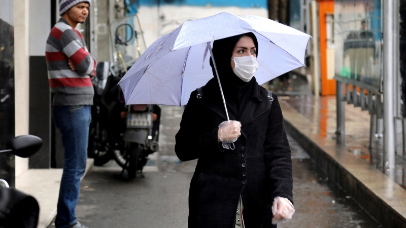 A pedestrian wears a mask and gloves to help guard against the Coronavirus, in downtown Tehran, Iran, Tuesday, Feb. 25, 2020. (AP Photo/Ebrahim Noroozi)
