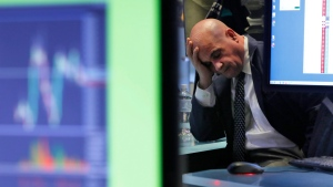 A specialist rests his head in his hand as he works on the floor of the New York Stock Exchange, Tuesday, Feb. 25, 2020. (AP / Richard Drew)