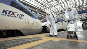 Workers wearing protective gears spray disinfectant as a precaution against the new coronavirus at Seoul Railway Station in Seoul, South Korea, Tuesday, Feb. 25, 2020. China and South Korea on Tuesday reported more cases of a new viral illness that has been concentrated in North Asia but is causing global worry as clusters grow in the Middle East and Europe. (Jin Yeon-soo/Yonhap via AP)
