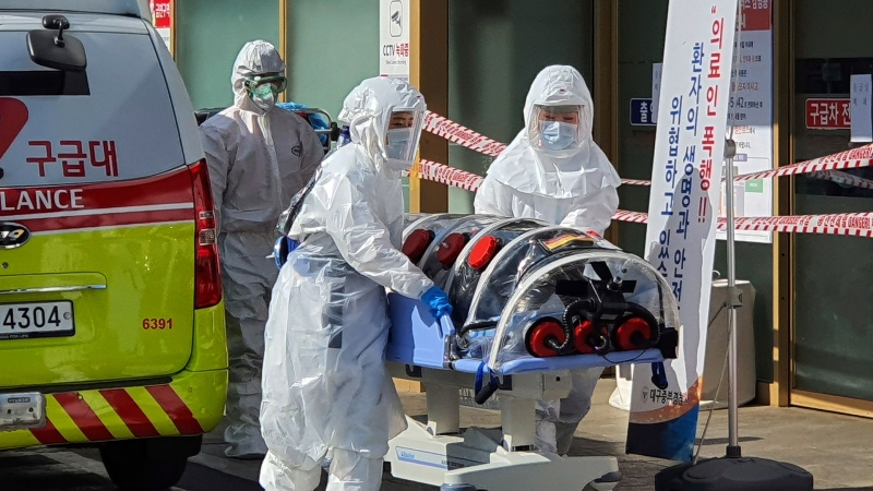 In this Wednesday, Feb. 19, 2020, file photo, medial workers wearing protective gears move a patient suspected of contracting the new coronavirus from an ambulance to the Kyungpook National University Hospital in Daegu, South Korea. In Daegu, most of the dozens of cases detected since Wednesday are linked to one church. (Kim Jong-un/Yonhap via AP, File)