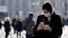A woman wearing a sanitary mask looks at her phone in Milan, Italy, Monday, Feb. 24, 2020. At least 190 people in Italy's north have tested positive for the COVID-19 virus and four people have died, including an 84-year-old man who died overnight in Bergamo, the Lombardy regional government reported. (Claudio Furlan/Lapresse via AP)