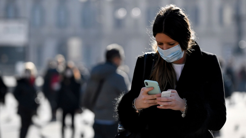 A woman wearing a sanitary mask looks at her phone in Milan, Italy, Monday, Feb. 24, 2020. (Claudio Furlan/Lapresse via AP)