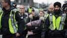 A woman, centre, is taken into custody by police officers enforcing an injunction against protesters who were blocking a road used to access to the Port of Vancouver, during a demonstration in support of Wet'suwet'en Nation hereditary chiefs attempting to halt construction of a natural gas pipeline on their traditional territory, in Vancouver, on Tuesday, February 25, 2020. THE CANADIAN PRESS/Darryl Dyck