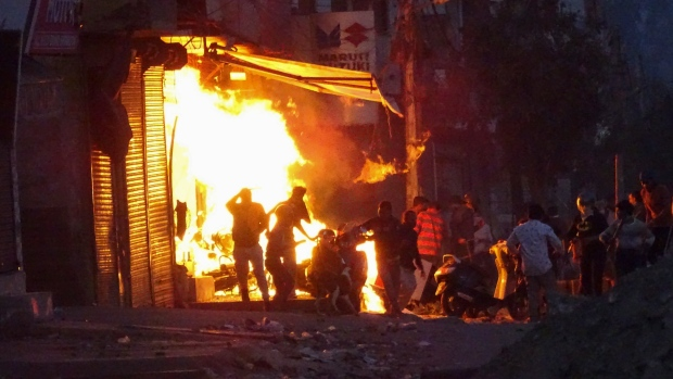 A shop is set on fire during violence between two groups in New Delhi, India, Tuesday, Feb. 25, 2020. (AP Photo)
