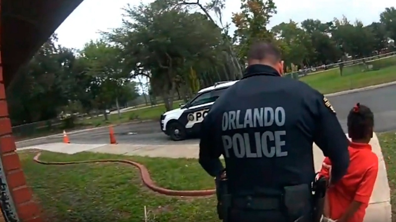 In this image taken from Sept. 19, 2019, Orlando Police Department body camera video footage, Orlando Police Officer Dennis Turner leads 6-year-old Kaia Rolle away after her arrest for kicking and punching staff members at the Lucious & Emma Nixon Academy Charter School in Orlando, Fla. (Orlando Police Department/Orlando Sentinel via AP)