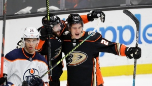 Anaheim Ducks left wing Sonny Milano, right, celebrates after scoring the winning goal with center Adam Henrique during overtime in an NHL hockey game against the Edmonton Oilers in Anaheim, Calif., Tuesday, Feb. 25, 2020. The Ducks won 4-3. (AP Photo/Chris Carlson)