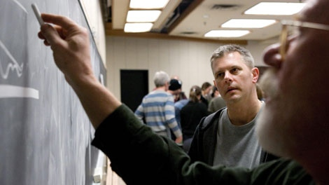Larry Epp (centre) watches as his tutor Sam Benvie draws on the chalk board during a class at The Chang School at Toronto's Ryerson University on Thursday, January 29, 2009. (Chris Young / THE CANADIAN PRESS)