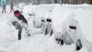 A woman shovels out her car during a snowstorm, Friday, February 7, 2020 in Montreal. THE CANADIAN PRESS/Ryan Remiorz