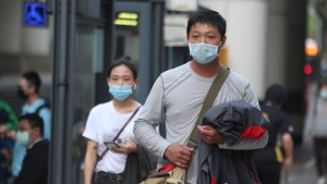 People wear face masks to protect against the spread of the coronavirus in Taipei, Taiwan, Wednesday, Feb. 26, 2020. (AP Photo/Chiang Ying-ying)