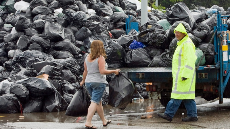 A Toronto city manager waits to accept residential garbage at the Birchmount Park temporary dump site during a strike involving members of CUPE Local 416 in 2009. Negotiations are continuing today to avert a work stoppage involving the city's outside workers that could begin as early as midnight. THE CANADIAN PRESS/Frank Gunn