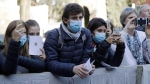 Faithful wear surgical masks as they wait for the arrival of Pope Francis outside the Santa Sabina Basilica in Rome, Wednesday, Feb. 26, 2020 amid an outbreak of coronavirus in Italy, which led to the cancellation of masses in northern regions of the country. (AP Photo/Gregorio Borgia)
