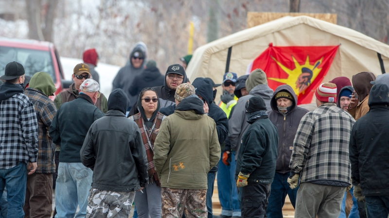Mohawks gather at the entrance to protest at a rail blockade in Kahnawake, Que. on Wednesday, February 26, 2020 in solidarity with the Wet'suwet'en hereditary chiefs opposed to the LNG pipeline in northern British Columbia. THE CANADIAN PRESS/Ryan Remiorz
