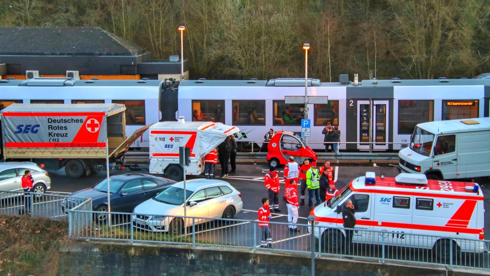 Emergency cars and police are standing at the station in Idar-Oberstein, Germany, Wednesday, Feb. 26, 2020 after a regional train with about 70 passengers was stopped on suspicion of a passenger having the coronavirus. (Sebastian Schmitt/dpa via AP)