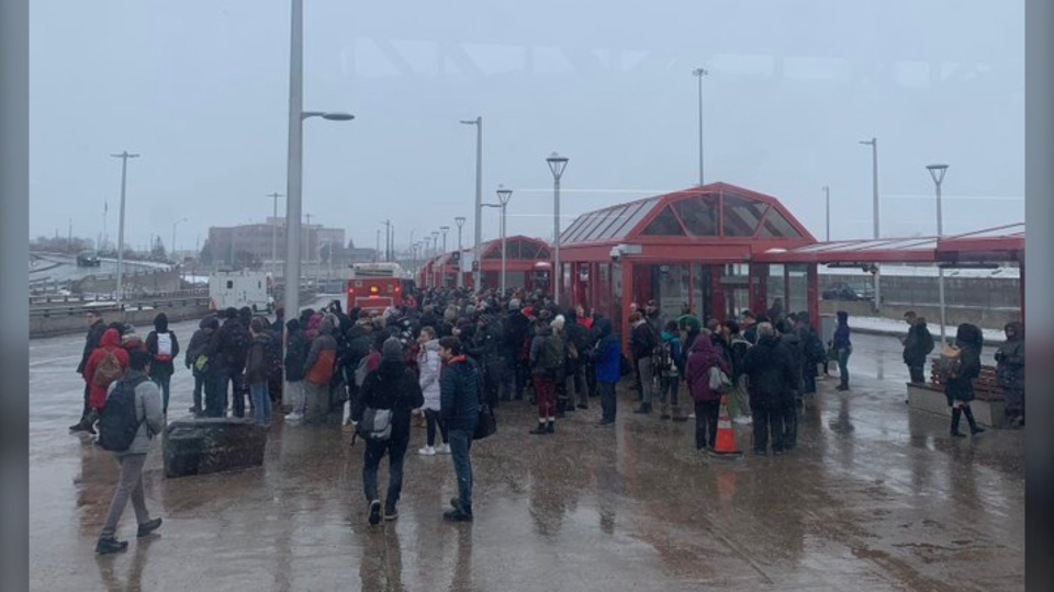 Passengers wait in the snow for R1 buses at St. Laurent Station after an overhead power component became loose on the line Feb. 26, 2020. (Photo courtesy of Ilan Shapiro / Twitter)