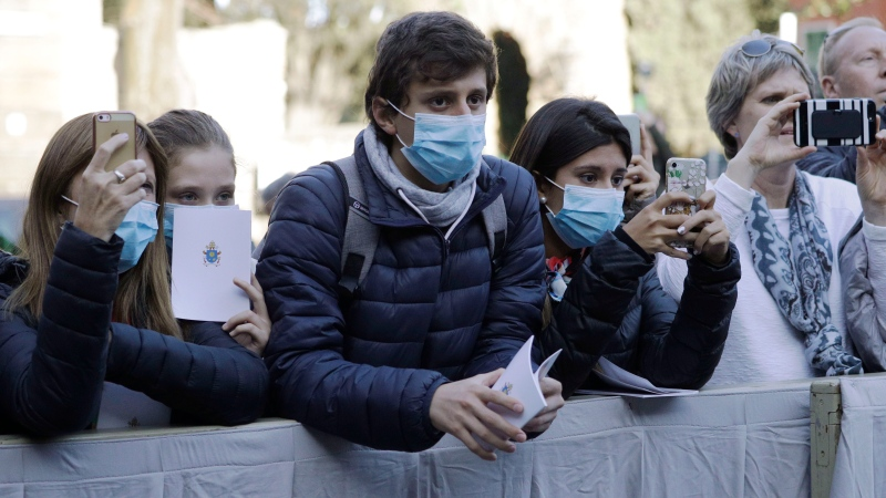 Faithful wear surgical masks as they wait for the arrival of Pope Francis outside the Santa Sabina Basilica on the occasion of the Ash Wednesday Mass opening Lent, the 40-day period of abstinence and deprivation for Christians before Holy Week and Easter, in Rome, Wednesday, Feb. 26, 2020. (AP Photo/Gregorio Borgia)