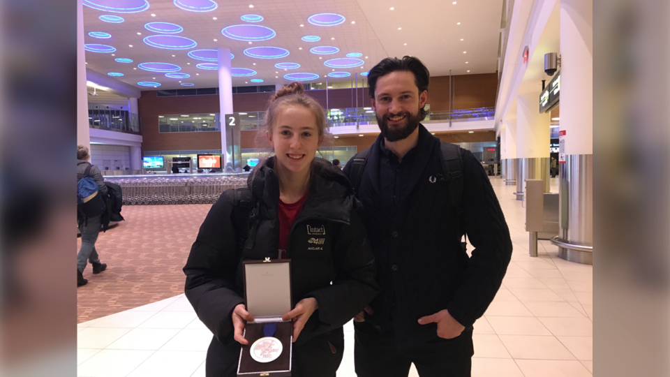 Alexa Scott showcases her medal with her coach Tyler Derraugh at the airport Tuesday night. (Source: Zachary Kitchen/ CTV News)