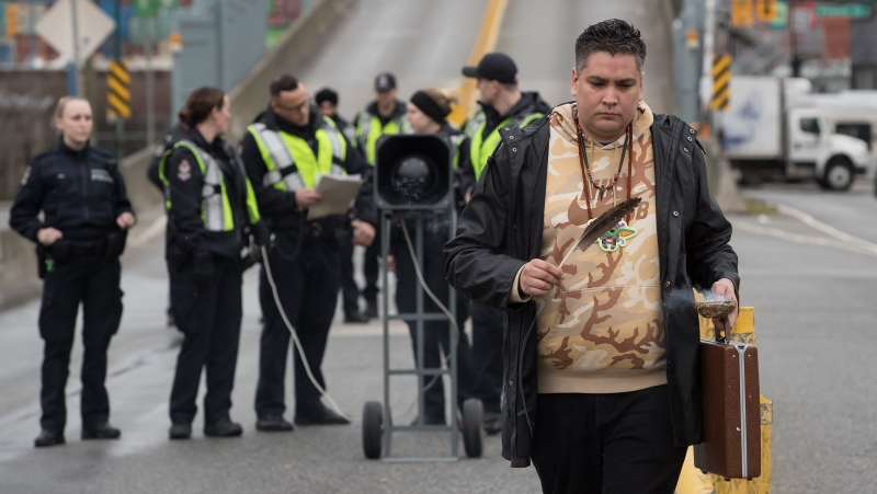 A man carries an eagle feather as police officers prepare to enforce an injunction against protesters who were blocking a road used to access to the Port of Vancouver, during a demonstration in support of Wet'suwet'en Nation hereditary chiefs attempting to halt construction of a natural gas pipeline on their traditional territory, in Vancouver, on Tuesday, February 25, 2020. THE CANADIAN PRESS/Darryl Dyck