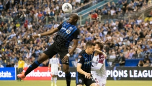 Montreal Impact's Rod Fanni heads the ball away from Deportivo Saprissa forward Manfred Ugalde (27) as defender Jukka Raitala covers during first half CONCACAF Champions League action in Montreal, Wednesday, Feb. 26, 2020. THE CANADIAN PRESS/Paul Chiasson