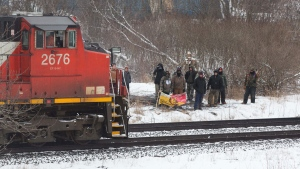Protesters stand next to the tracks as a CN train moves through Tyendinaga Mohawk Territory, near Belleville, Ont., on Wednesday Feb. 26, 2020, as they protest in solidarity with the Wet'suwet'en hereditary chiefs opposed to the LNG pipeline in northern British Columbia. THE CANADIAN PRESS/Lars Hagberg