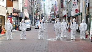 South Korean soldiers wearing a protective suits spray disinfectant to prevent the spread of the COVID-19 on a street in Daegu, South Korea, Thursday, Feb. 27, 2020. (Kim Hyun-tai/Yonhap via AP)