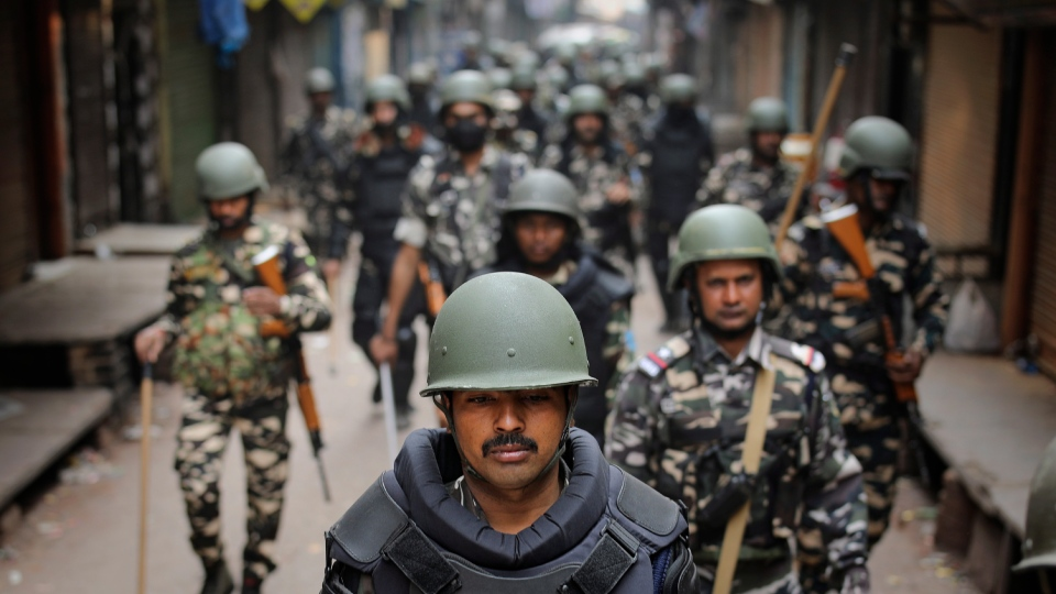 Indian security officers patrol a street in New Delhi, India, Wednesday, Feb. 26, 2020. (AP Photo/Altaf Qadri)