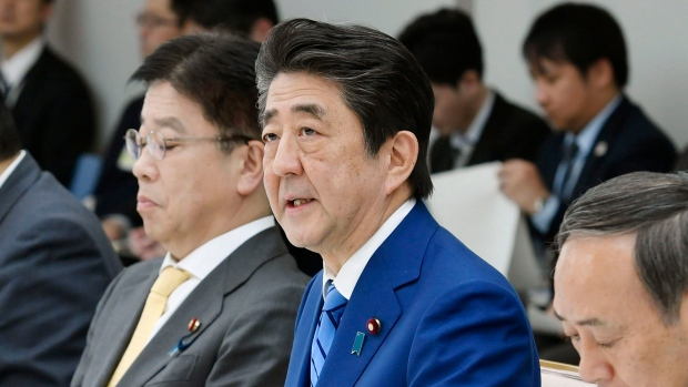 Japan's Prime Minister Shinzo Abe, center, speaks during a meeting of a task force on the new coronavirus at his official residence in Tokyo Thursday, Feb. 27, 2020. (Kyodo News via AP)