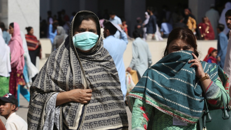 Pakistani women wearing face masks leave the Aga Khan hospital where a patient suspected of having contracted coronavirus was admitted, in Karachi, Pakistan, Thursday, Feb. 27, 2020. (AP Photo/Fareed Khan)