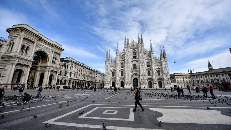 A small number of people walk through the Piazza Duomo in Milan Wednesday, Feb. 26, 2020. The viral outbreak that began in China and has infected more than 80,000 people globally, so far caused 374 cases and 12 deaths in Italy, according to the last figures released by civil protection. (Claudio Furlan/LaPresse via AP)