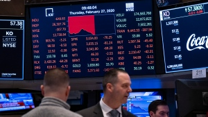 Stocks reflect declines on monitors as people work on the floor of the New York Stock Exchange Thursday, Feb. 27, 2020. (AP Photo/Craig Ruttle)