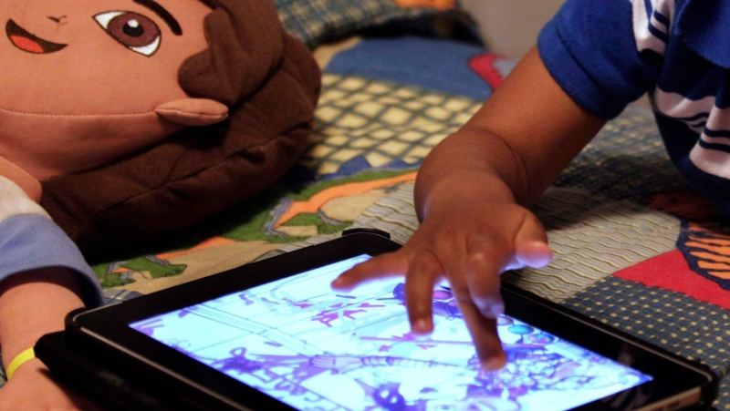 A child plays with an iPad in his bedroom in Metairie, La., on October 21, 2011. THE CANADIAN PRESS/AP, Gerald Herbert