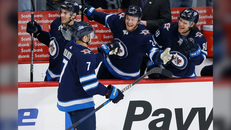 Winnipeg Jets' Dmitry Kulikov (7), Anthony Bitetto (2) and Nathan Beaulieu (88) celebrate Kulikov's goal against the Washington Capitals during first period NHL action in Winnipeg on Thursday, February 27, 2020. (THE CANADIAN PRESS/John Woods)