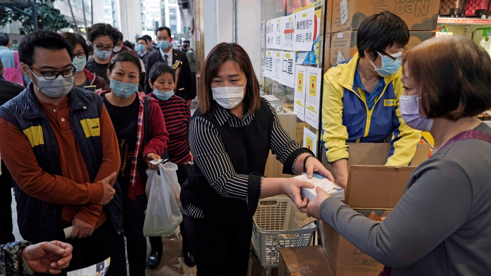 FILE - In this Feb. 7, 2020, file photo, people queue up to buy face masks in Hong Kong. (AP Photo/Kin Cheung, File)