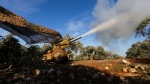 Turkish backed rebel fighters fire a howitzer toward Syrian government's forces positions near the village of Neirab in Idlib province, Syria, Thursday, Feb. 20, 2020. (AP Photo/Ghaith Alsayed)