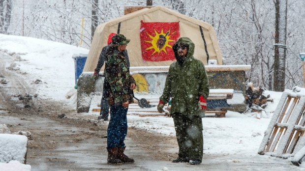 Protesters in support of the Wet'suwet'en hereditary chiefs stand near the entrance to the blockade of the commuter rail line in Kahnawake Mohawk Territory, near Montreal, Thursday, Feb. 27, 2020. THE CANADIAN PRESS/Ryan Remiorz