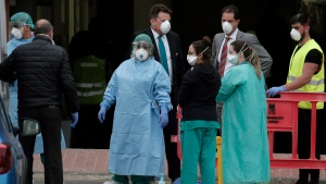 Health personnel wearing protection clothing look on as guests prepare to leave the H10 Costa Adeje Palace hotel in La Caleta, in the Canary Island of Tenerife, Spain, Friday Feb. 28, 2020. (AP Photo/Joan Mateu)