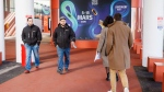 People pass a advertisement board at the 90th Geneva International Motor Show, GIMS, at Palexpo, in Geneva, Switzerland, Friday, Feb. 28, 2020. (Salvatore di Nolfi/Keystone via AP)