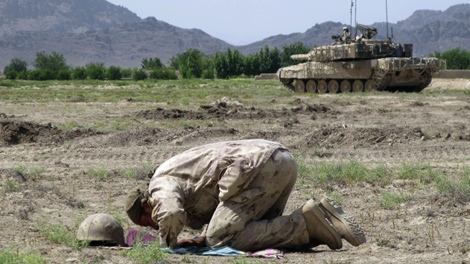An Afghan military interpreter prays just before the storming of Salavat, Afghanistan, on Thursday, June 18, 2009. Canadian and Afghan soldiers descended on the town in a hunt for insurgents and their weapons. (Colin Perkel / THE CANADIAN PRESS)