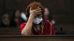 A woman wears a surgical mask as a precaution against the spread of the new coronavirus COVID-19 during a Mass commemorating Ash Wednesday at the Cathedral in Mexico City, Wednesday, Feb. 26, 2020. (AP Photo/Fernando Llano)