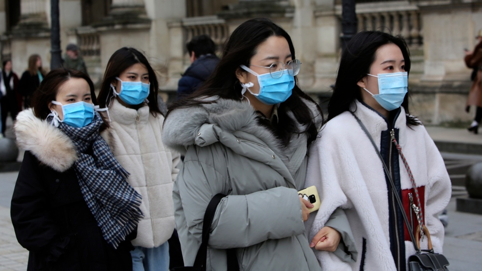 Tourists wearing a mask walks outside the Louvre museum Friday, Feb. 28, 2020 in Paris. (AP Photo/Rafael Yaghobzadeh)