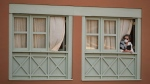 A woman looks out of a window at the H10 Costa Adeje Palace hotel in La Caleta, in the Canary Island of Tenerife, Spain, Wednesday, Feb. 26, 2020. (AP Photo)