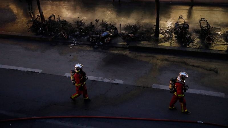 Firefighters walk past charred vehicles after a fire near the Gare de Lyon train station Friday, Feb. 28, 2020 in Paris. (AP Photo/Francois Mori)
