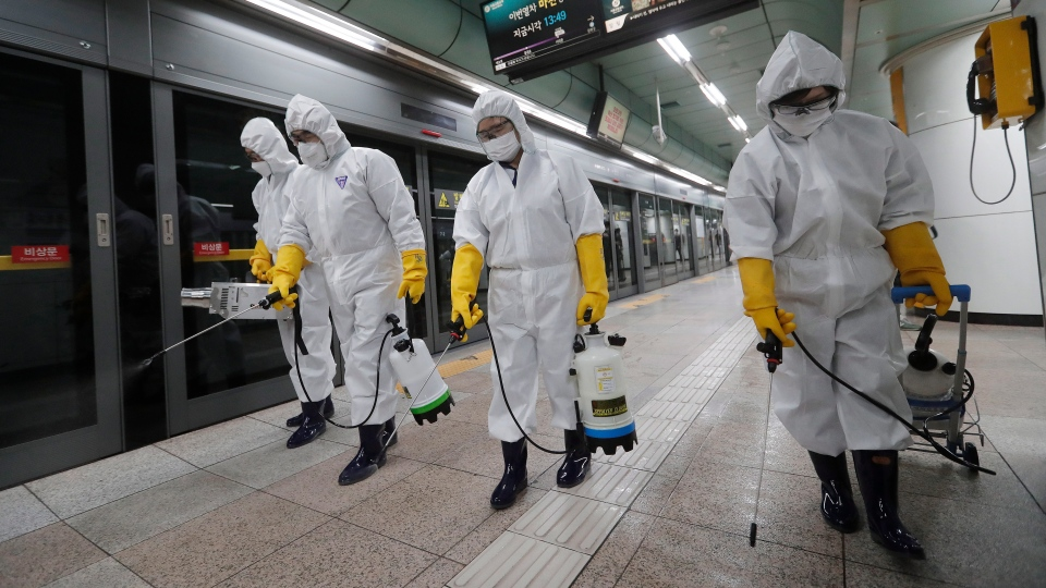 Workers wearing protective gears spray disinfectant as a precaution against the new coronavirus at a subway station in Seoul, South Korea, Friday, Feb. 28, 2020. (AP Photo/Ahn Young-joon)