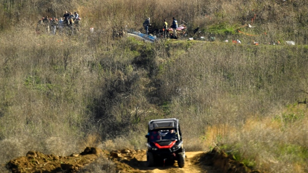 In this Monday, Jan. 27, 2020 file photo, investigators, top, work the scene of a helicopter crash that killed former NBA basketball player Kobe Bryant, his 13-year-old daughter, Gianna, and seven others as Los Angeles County Sheriff's deputies patrol in an all-terrain vehicle on a hillside in Calabasas, Calif. (AP Photo/Mark J. Terrill, File)