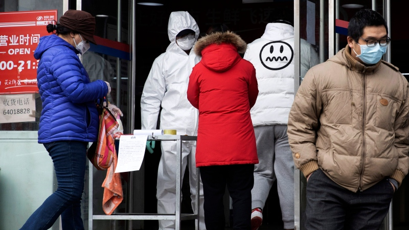 In this Thursday, Feb. 27, 2020, file photo, a worker in overalls screen for fever at the entrance to a supermarket in Beijing. Health officials reported the first U.S. drug shortage tied to the viral outbreak that is disrupting production in China, but they declined to identify the manufacturer or the product. The Food and Drug Administration said late Thursday, that the drug's maker contacted health officials recently about the shortage, which it blamed on a manufacturing issue with the medicine's key ingredient. (AP Photo/Ng Han Guan, File)