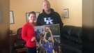 Randy Mulder, right, and his wife Claire proudly display a photo of their son Mychal, who made his NBA debut with the Golden State Warriors Thursday night. (Courtesy Randy Mulder)