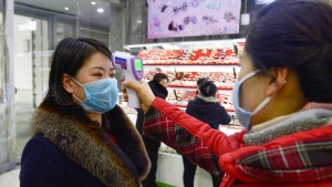 In this Friday, Feb. 28, 2020, photo, a clerk checks the temperature of a shopper at a department store amid growing concern over the coronavirus outbreak in Pyongyang, North Korea.  (Kyodo News via AP)