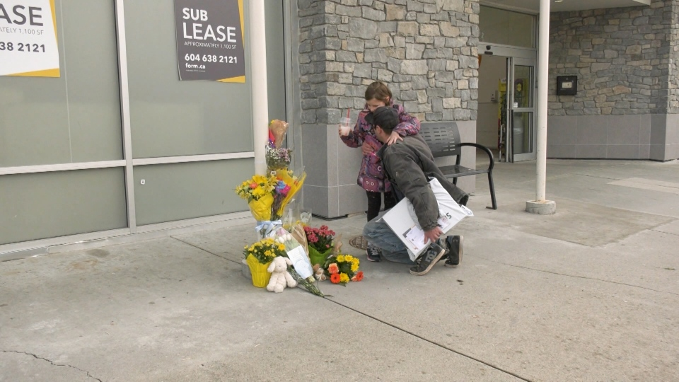 One after another, shoppers brought flowers to a growing memorial outside the store Saturday. (CTV)