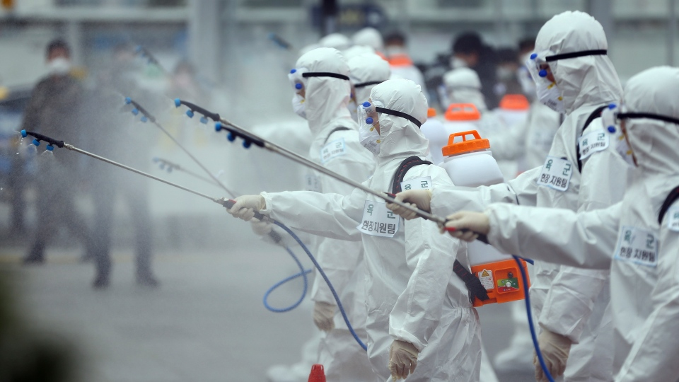 Army soldiers wearing protective suits spray disinfectant to prevent the spread of the new coronavirus at the Dongdaegu train station in Daegu, South Korea, Saturday, Feb. 29, 2020. (Kim Hyun-tai/Yonhap via AP)