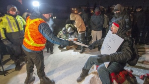 Police serve an injunction to protesters at a rail blockade in St-Lambert, south of Montreal on Thursday, February 20, 2020. As demonstrations continue across Canada in support of Wet'suwet'en hereditary chiefs opposing a pipeline through their territory, legal experts suggest it's time to reconsider how injunctions are employed when responding to Indigenous-led protests.THE CANADIAN PRESS/Ryan Remiorz